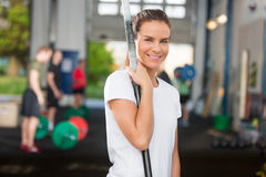 Attractive and smiling woman at crossfit center. Fit young and happy woman rests after workout at a crossfit fitness center. People workout in the background Royalty Free Stock Photos