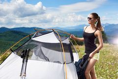 Woman tourist hiking in mountain trail, enjoying summer sunny morning in mountains near tent. Attractive smiling woman hiker hiking mountain trail, standing near stock photo