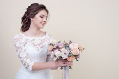 Attractive smiling woman holding a bouquet of flowers wearing in luxurious wedding dress isolated on background. Concept of wedding hairstyle, makeup and Stock Images