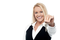 Attractive smiling woman holding a key stock photography