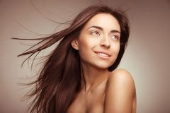 Attractive smiling woman with long hair on grey Royalty Free Stock Image