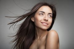 Attractive smiling woman with long hair on grey Stock Images