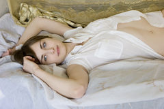Attractive smiling woman lying on bed Royalty Free Stock Photography
