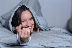 An attractive smiling woman, lying in bed under a blanket, looking at the camera, invited with a gesture to her. Attractive smiling woman, lying in bed under a Stock Images