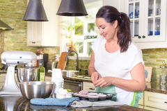 Attractive smiling woman making cookies in sunny kitchen Royalty Free Stock Photos
