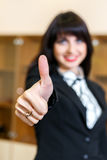 Attractive smiling woman in office shows thumb up Stock Images