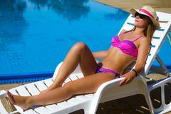 Sunbathing woman at poolside. The attractive smiling woman in pink bikini and hat is sunbathing at the poolside Stock Image