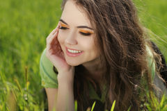 Attractive smiling woman resting on green grass, outdoors portra Stock Photography