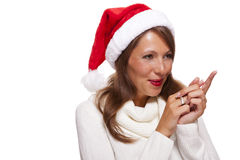 Attractive smiling woman in a Santa hat. Attractive smiling woman in a festive red Santa hat pointing towards blank copyspace for our Christmas advertising, text Stock Images