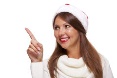 Attractive smiling woman in a Santa hat. Attractive smiling woman in a festive red Santa hat pointing towards blank copyspace for our Christmas advertising, text Stock Image