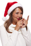 Attractive smiling woman in a Santa hat. Attractive smiling woman in a festive red Santa hat pointing towards blank copyspace for our Christmas advertising, text Stock Photos
