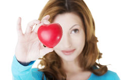 Attractive smiling woman showing red heart Stock Images