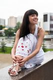 Attractive smiling woman sits over city background Stock Photos
