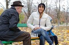 Attractive smiling woman sitting on a park bench playing chess with an elderly man. Attractive smiling women sitting park bench playing chess an elderly men Royalty Free Stock Photos