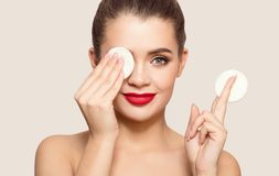 Attractive smiling woman using cotton pad. royalty free stock photo