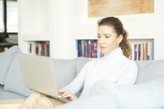 Surfing on the internet from my cosy sofa. An attractive smiling woman using her laptop while relaxing at home on the sofa Royalty Free Stock Images