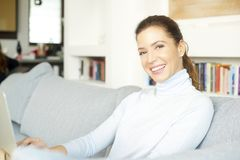 Surfing on the internet from my cosy sofa. An attractive smiling woman using her laptop while relaxing at home on the sofa Royalty Free Stock Photography
