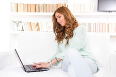 Attractive smiling woman using laptop computer keyboard on sofa Royalty Free Stock Images