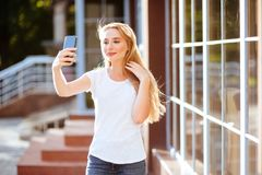 Attractive smiling woman using smartphone outdoors. royalty free stock image
