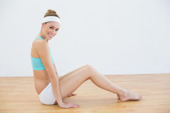 Attractive smiling woman wearing sportswear sitting on floor in sports hall Royalty Free Stock Photos