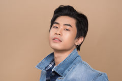 Attractive smiling young asian man against light background Stock Photo