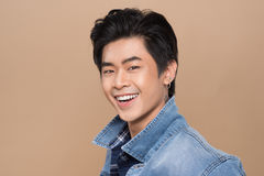 Attractive smiling young asian man against light background Royalty Free Stock Image