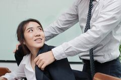 Attractive smiling young Asian woman are cared for by colleagues.  Man and woman flirting in office. Love and romance couple in