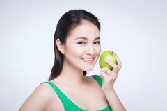 Attractive smiling young asian woman eating green apple isolated over white background stock photography