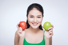 Attractive smiling young asian woman holding green apple isolated over white background royalty free stock image