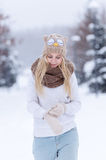 Attractive smiling young blonde girl walking in winter forest. Pretty woman in wintertime outdoor. Wearing winter clothes. Stock Photos