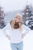 Attractive smiling young blonde girl walking in winter forest. Pretty woman in wintertime outdoor. Wearing winter clothes. Royalty Free Stock Photo