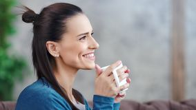 Attractive smiling young brunette woman dreaming and drinking hot beverage medium close-up stock footage