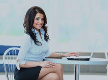 Attractive smiling young business woman using laptop at work desk. Stock Photo