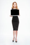 Attractive smiling young businesswoman standing and holding blank screen laptop Royalty Free Stock Photos