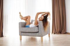 Attractive smiling young girl lying on armchair and posing looking at camera Stock Images