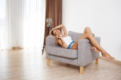 Attractive smiling young girl lying on armchair and talking on phone  at living room Stock Photos