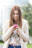 Attractive smiling young girl using phone in the street. Stock Photography