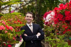 Attractive smiling young men in a business suit in a flower garden Royalty Free Stock Photo