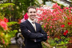 Attractive smiling young men in a business suit in a flower garden Stock Photos
