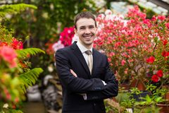 Attractive smiling young men in a business suit in a flower garden Stock Photography