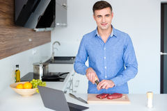 Attractive smiling young man cooking meat on the kitchen Royalty Free Stock Image