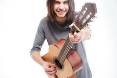 Attractive smiling young man with long hair playing acoustic guitar Royalty Free Stock Photography