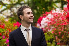Attractive smiling young men in a business suit in a flower garden Royalty Free Stock Image