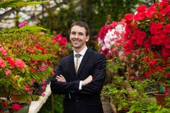 Attractive smiling young men in a business suit in a flower garden Stock Photo