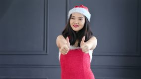 Attractive smiling young Santa Claus woman showing thumbs up cool gesture. Happy beautiful Christmas Asian girl enjoying and having good time at studio