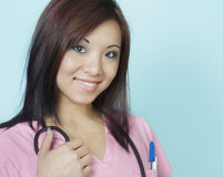 Attractive smiling young student nurse. Doctor wearing pink scrubs Royalty Free Stock Image