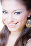 Attractive smiling young woman with ear-rings Royalty Free Stock Image