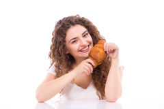 Attractive smiling young woman eating croissant for breakfast at table. On white background Stock Photography