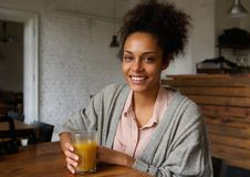 Attractive smiling young woman with fruit juice drink Stock Photography