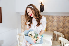 Attractive smiling young woman holding bouquet of flowers in cafe Royalty Free Stock Photography